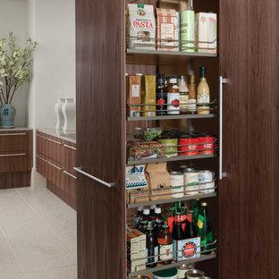 ヒューストンの広いモダンスタイルのおしゃれなキッチン (シングルシンク、フラットパネル扉のキャビネット、茶色いキャビネット、クオーツストーンカウンター、シルバーの調理設備、磁器タイルの床、グレーの床) の写真