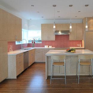 Foto de cocina en L, moderna, con electrodomésticos con paneles, salpicadero rojo, puertas de armario de madera clara, armarios con paneles lisos y fregadero de doble seno