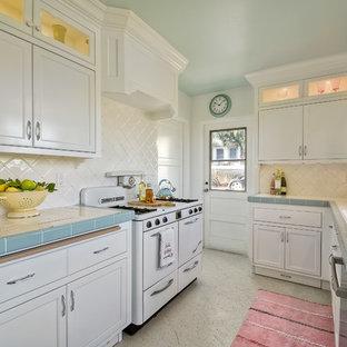 Geschlossene, Zweizeilige, Mittelgroße Klassische Küche ohne Insel mit Doppelwaschbecken, Schrankfronten mit vertiefter Füllung, weißen Schränken, Arbeitsplatte aus Fliesen, Küchenrückwand in Weiß, Rückwand aus Keramikfliesen, weißen Elektrogeräten und Terrazzo-Boden in San Diego