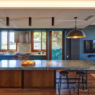 Tropical galley kitchen in Sydney with an undermount sink, flat-panel cabinets, blue cabinets, stainless steel appliances, dark hardwood floors, with island, brown floor, grey benchtop and recessed.