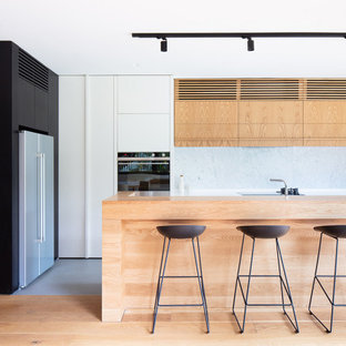 This is an example of a large contemporary l-shaped open plan kitchen in Melbourne with light wood cabinets, laminate benchtops, white splashback, stone slab splashback, with island, flat-panel cabinets and grey floor.