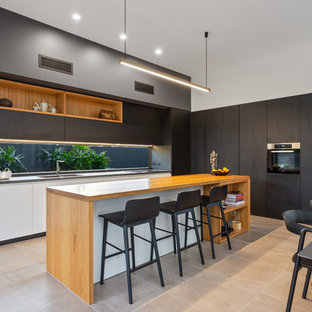This is an example of a contemporary l-shaped eat-in kitchen in Gold Coast - Tweed with a double-bowl sink, flat-panel cabinets, black cabinets, wood benchtops, window splashback, with island, beige floor and brown benchtop.