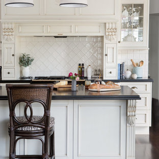 Traditional kitchen in Brisbane with recessed-panel cabinets, beige cabinets, white splashback, dark hardwood floors, with island, brown floor and black benchtop.