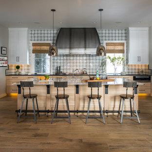 Klassisk inredning av ett kök, med skåp i shakerstil, vita skåp, flerfärgad stänkskydd, rostfria vitvaror, mellanmörkt trägolv och en köksö