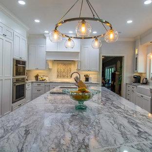 タンパの広いトランジショナルスタイルのおしゃれなキッチン (ドロップインシンク、フラットパネル扉のキャビネット、白いキャビネット、御影石カウンター、ベージュキッチンパネル、セラミックタイルのキッチンパネル、シルバーの調理設備、淡色無垢フローリング) の写真