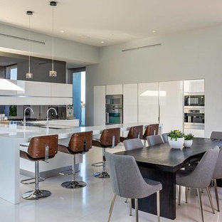 Contemporary eat-in kitchen appliance - Eat-in kitchen - contemporary gray floor eat-in kitchen idea in Los Angeles with flat-panel cabinets, white cabinets, mirror backsplash, stainless steel appliances, a peninsula and gray countertops