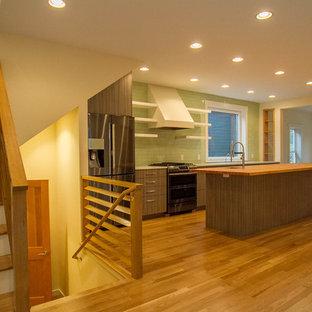 シアトルの中サイズのコンテンポラリースタイルのおしゃれなキッチン (アンダーカウンターシンク、フラットパネル扉のキャビネット、濃色木目調キャビネット、木材カウンター、緑のキッチンパネル、セメントタイルのキッチンパネル、シルバーの調理設備、無垢フローリング、茶色い床) の写真