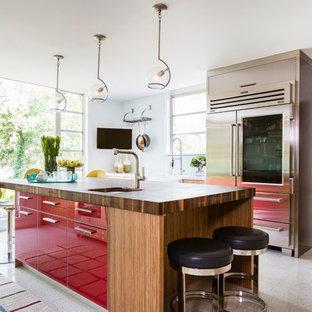Foto de cocina retro con fregadero sobremueble, armarios con paneles lisos, puertas de armario rojas, encimera de madera, salpicadero blanco, salpicadero de vidrio templado, electrodomésticos de acero inoxidable, suelo de terrazo y una isla