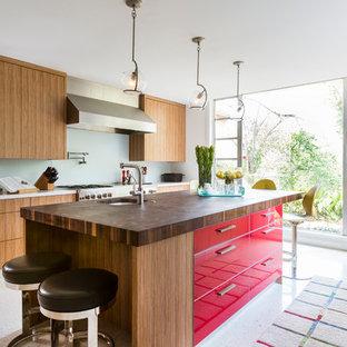 Modelo de cocina retro con fregadero sobremueble, armarios con paneles lisos, puertas de armario rojas, encimera de madera, salpicadero blanco, salpicadero de vidrio templado, electrodomésticos de acero inoxidable, suelo de terrazo y una isla