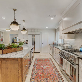 Large eclectic l-shaped open plan kitchen in Dallas with a farmhouse sink, shaker cabinets, white cabinets, soapstone benchtops, grey splashback, ceramic splashback, stainless steel appliances, travertine floors, with island, beige floor and black benchtop.