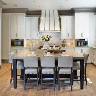 Large transitional eat-in kitchen remodeling - Example of a large transitional l-shaped light wood floor eat-in kitchen design in Houston with white cabinets, concrete countertops, white backsplash, stone slab backsplash, shaker cabinets and paneled appliances