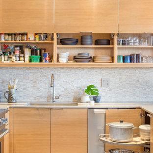 Неиссякаемый источник вдохновения для домашнего уюта: п-образная кухня-гостиная среднего размера в современном стиле с врезной раковиной, плоскими фасадами, светлыми деревянными фасадами, столешницей из кварцевого композита, бежевым фартуком, фартуком из каменной плитки, техникой из нержавеющей стали, паркетным полом среднего тона и полуостровом