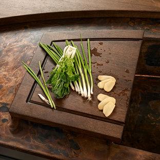 Asiatische Küche mit hellen Holzschränken, Kupfer-Arbeitsplatte, Küchenrückwand in Grün, Rückwand aus Stein und schwarzen Elektrogeräten in Sonstige