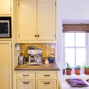 Design ideas for a mid-sized traditional u-shaped separate kitchen in Albuquerque with a farmhouse sink, shaker cabinets, yellow cabinets, concrete benchtops, yellow splashback, ceramic splashback, stainless steel appliances, dark hardwood floors, with island and brown floor.