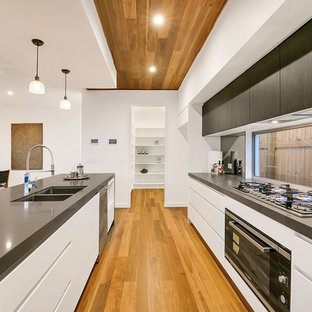 Photo of a contemporary galley open plan kitchen in Brisbane with a double-bowl sink, flat-panel cabinets, white cabinets, window splashback, black appliances, medium hardwood floors, with island, brown floor and grey benchtop.