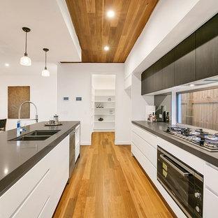 Offene, Zweizeilige Moderne Küche mit Doppelwaschbecken, flächenbündigen Schrankfronten, weißen Schränken, Rückwand-Fenster, schwarzen Elektrogeräten, braunem Holzboden, Kücheninsel, braunem Boden und grauer Arbeitsplatte in Brisbane