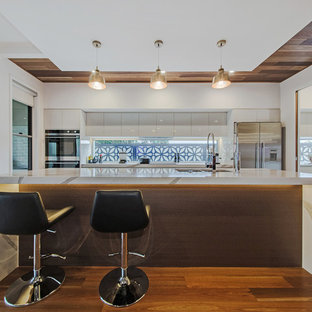 Inspiration for a mid-sized contemporary galley kitchen in Brisbane with a double-bowl sink, white cabinets, window splashback, medium hardwood floors, with island, brown floor, flat-panel cabinets, stainless steel appliances and multi-coloured benchtop.