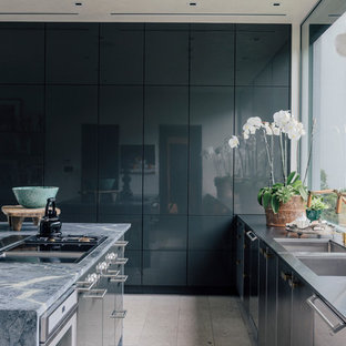 Design ideas for a contemporary galley kitchen in New York with an undermount sink, flat-panel cabinets, with island, limestone benchtops, stainless steel appliances, porcelain floors and grey floor.