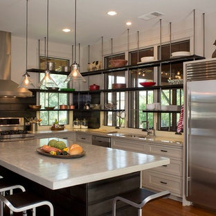 Photo of a mid-sized contemporary l-shaped kitchen in Austin with concrete benchtops, an undermount sink, shaker cabinets, white cabinets, black splashback, stainless steel appliances, light hardwood floors and with island.
