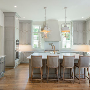 Large traditional kitchen designs - Inspiration for a large timeless u-shaped medium tone wood floor kitchen remodel in Austin with paneled appliances, an island, an undermount sink, recessed-panel cabinets, gray cabinets, white backsplash and white countertops