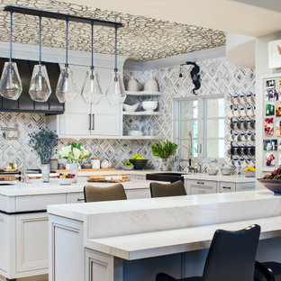 This is an example of an eclectic u-shaped kitchen in Los Angeles with a farmhouse sink, recessed-panel cabinets, grey cabinets, multi-coloured splashback, stainless steel appliances, multiple islands, white benchtop and wallpaper.