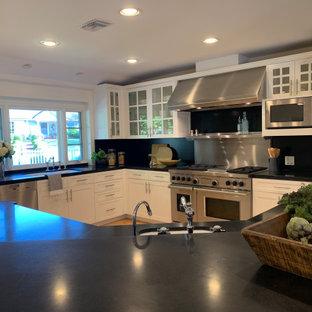 Esempio di una grande cucina country con lavello a doppia vasca, ante di vetro, ante bianche, top in granito, paraspruzzi nero, paraspruzzi in granito, elettrodomestici in acciaio inossidabile, pavimento in legno massello medio, isola e top nero