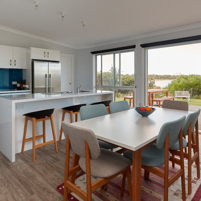 Eat-in kitchen - contemporary galley medium tone wood floor and brown floor eat-in kitchen idea in Other with a drop-in sink, flat-panel cabinets, white cabinets, blue backsplash, glass sheet backsplash, stainless steel appliances, an island and white countertops