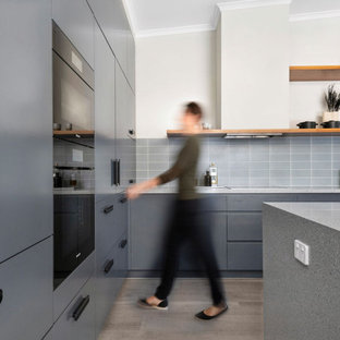 Design ideas for a mid-sized contemporary l-shaped kitchen pantry in Canberra - Queanbeyan with an undermount sink, flat-panel cabinets, blue cabinets, terrazzo benchtops, blue splashback, subway tile splashback, black appliances, laminate floors, with island, beige floor, blue benchtop and vaulted.