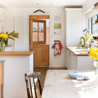 Country u-shaped kitchen/diner in Surrey with a built-in sink, shaker cabinets, white cabinets, wood worktops, multi-coloured splashback, medium hardwood flooring, a breakfast bar, brown floors and brown worktops.