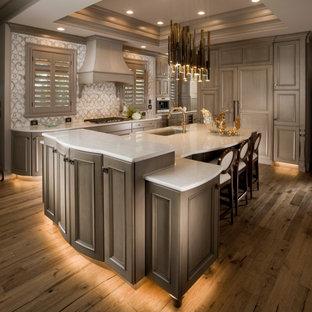 Exempel på ett stort klassiskt vit vitt kök med öppen planlösning, med en enkel diskho, luckor med infälld panel, beige skåp, bänkskiva i kvarts, beige stänkskydd, stänkskydd i porslinskakel, integrerade vitvaror, mellanmörkt trägolv, en köksö och brunt golv