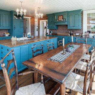 Immagine di una cucina country di medie dimensioni con lavello stile country, ante con bugna sagomata, ante blu, top in legno, paraspruzzi rosso, paraspruzzi in mattoni, elettrodomestici da incasso, parquet scuro, isola, pavimento marrone e top marrone