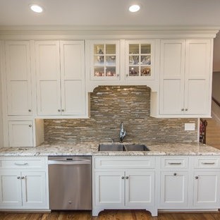 This is an example of a rural l-shaped kitchen/diner in Birmingham with a submerged sink, shaker cabinets, white cabinets, granite worktops, stainless steel appliances, plywood flooring and an island.