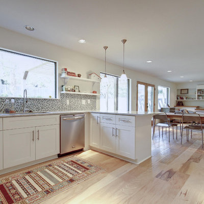 Open concept kitchen - eclectic open concept kitchen idea in Austin with mosaic tile backsplash, stainless steel appliances, white cabinets, shaker cabinets and multicolored backsplash