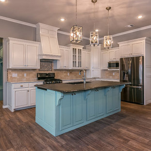 Mid-sized traditional eat-in kitchen inspiration - Mid-sized elegant l-shaped porcelain tile eat-in kitchen photo in Dallas with an undermount sink, brown backsplash, stainless steel appliances, an island, raised-panel cabinets, white cabinets, granite countertops and ceramic backsplash