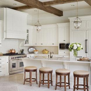 アトランタの広いトラディショナルスタイルのおしゃれなキッチン (レイズドパネル扉のキャビネット、白いキャビネット、白いキッチンパネル、サブウェイタイルのキッチンパネル、パネルと同色の調理設備、アンダーカウンターシンク、御影石カウンター、ライムストーンの床) の写真