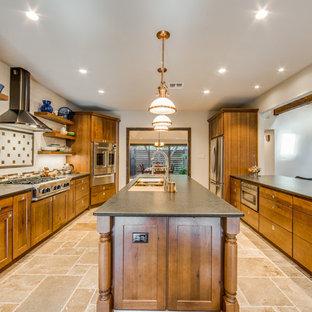 オースティンの広いトランジショナルスタイルのおしゃれなキッチン (ドロップインシンク、フラットパネル扉のキャビネット、濃色木目調キャビネット、御影石カウンター、茶色いキッチンパネル、セラミックタイルのキッチンパネル、シルバーの調理設備、トラバーチンの床、ベージュの床、黒いキッチンカウンター) の写真