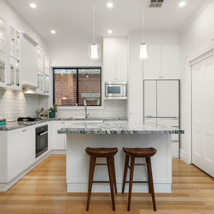 Inspiration for a contemporary l-shaped kitchen in Melbourne with white splashback, multi-coloured benchtop, shaker cabinets, white cabinets, ceramic splashback, white appliances, light hardwood floors, with island and beige floor.