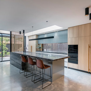Inspiration for a large contemporary galley open plan kitchen in Melbourne with a drop-in sink, light wood cabinets, window splashback, black appliances, concrete floors, with island, grey floor, flat-panel cabinets and grey benchtop.