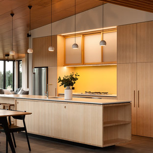 Photo of a mid-sized contemporary galley eat-in kitchen in Auckland with raised-panel cabinets, light wood cabinets, yellow splashback, glass sheet splashback, stainless steel appliances, porcelain floors and with island.