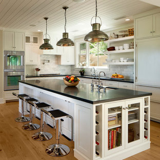 Large traditional kitchen pictures - Inspiration for a large timeless l-shaped light wood floor kitchen remodel in Santa Barbara with an undermount sink, shaker cabinets, white cabinets, white backsplash, paneled appliances, an island and black countertops