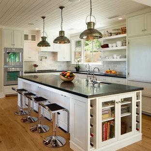 Klassisk inredning av ett stort svart svart l-kök, med en undermonterad diskho, skåp i shakerstil, vita skåp, vitt stänkskydd, integrerade vitvaror, en köksö och ljust trägolv