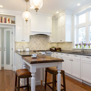 Mid-sized elegant u-shaped medium tone wood floor enclosed kitchen photo in Other with a single-bowl sink, recessed-panel cabinets, white cabinets, quartz countertops, beige backsplash, ceramic backsplash, stainless steel appliances and a peninsula