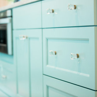 Inspiration for a small beach style l-shaped eat-in kitchen in Other with an undermount sink, flat-panel cabinets, turquoise cabinets, quartz benchtops, white splashback, ceramic splashback, stainless steel appliances, vinyl floors, with island and grey floor.