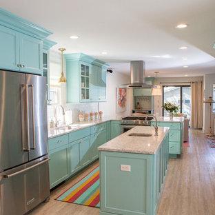 他の地域の小さいビーチスタイルのおしゃれなキッチン (アンダーカウンターシンク、フラットパネル扉のキャビネット、ターコイズのキャビネット、クオーツストーンカウンター、白いキッチンパネル、セラミックタイルのキッチンパネル、シルバーの調理設備、クッションフロア、グレーの床) の写真