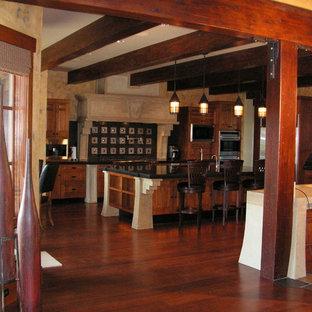 他の地域の大きいアジアンスタイルのおしゃれなキッチン (アンダーカウンターシンク、レイズドパネル扉のキャビネット、中間色木目調キャビネット、ソープストーンカウンター、黒いキッチンパネル、磁器タイルのキッチンパネル、シルバーの調理設備の、無垢フローリング) の写真