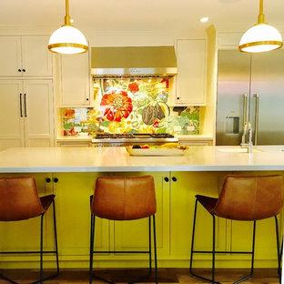 サンフランシスコの大きいカントリー風おしゃれなキッチン (エプロンフロントシンク、マルチカラーのキッチンパネル、ガラス板のキッチンパネル、シルバーの調理設備の、茶色い床、無垢フローリング、シェーカースタイル扉のキャビネット、白いキャビネット、珪岩カウンター) の写真