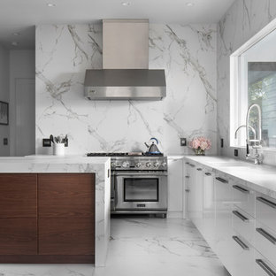 Contemporary kitchen photos - Kitchen - contemporary l-shaped white floor kitchen idea in Orlando with an undermount sink, flat-panel cabinets, white cabinets, white backsplash, stainless steel appliances, an island and white countertops