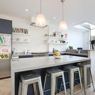 ロンドンの中サイズのコンテンポラリースタイルのおしゃれなキッチン (フラットパネル扉のキャビネット、青いキャビネット、白いキッチンパネル、レンガのキッチンパネル、シルバーの調理設備の、淡色無垢フローリング、ベージュの床、グレーのキッチンカウンター、アンダーカウンターシンク) の写真