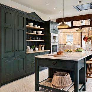 Ispirazione per una cucina parallela chic con ante con riquadro incassato, ante verdi, elettrodomestici in acciaio inossidabile, parquet chiaro e isola