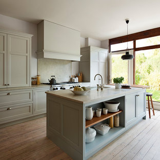 This is an example of a country galley kitchen in Oxfordshire with raised-panel cabinets, grey cabinets, grey splashback, light hardwood flooring, an island and brown floors.